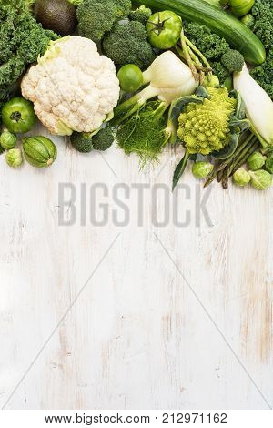 Top view of green vegetables on the white wooden table, copy space for text on the bottom, vertical, selective focus