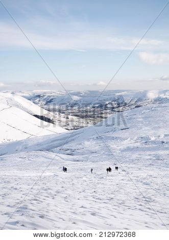 PEAK DISTRICT UK - CIRCA 2012: A group of hikers climbs Kinder Scout in winter with Edale valley in the distance. Peak District UK