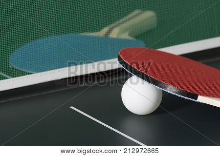 Ping Pong Paddles On Table With Net, One Out Of Focus