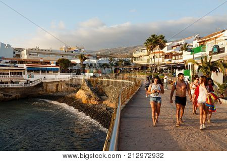 TENERIFE SPAIN - CIRCA 2015: Spanish tourists walk along the seafront in La Caleta Tenerife Canary Islands