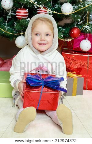 A sweet little four year old girl with a gift in her hands on Christmas.The girl is sitting on the floor holding a box with a gift.