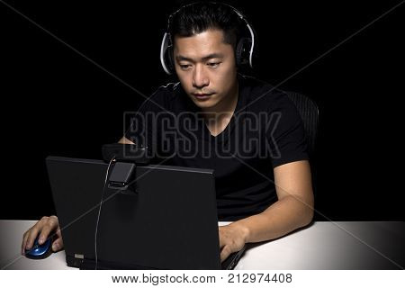 Competitive asian male professional E Sports video gamer playing an FPS or MMO game on a computer and streaming online.