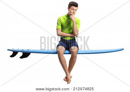 Pensive teen surfer sitting on a surfboard isolated on white background