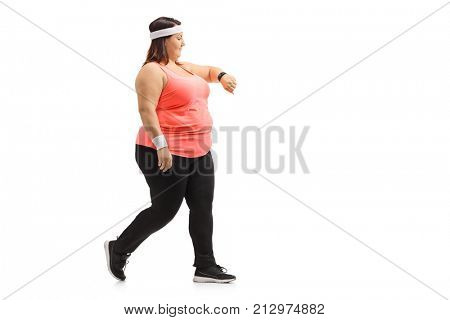 Full length profile shot of an overweight woman walking and checking her sports watch isolated on white background