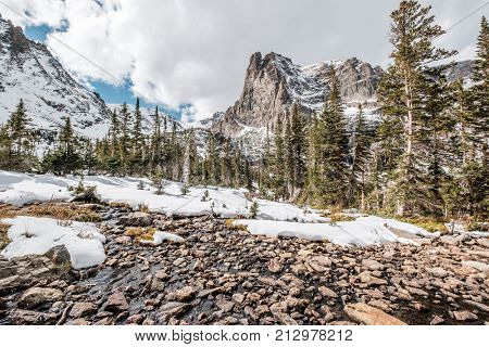 Lake Helene with rocks and mountains in snow around at autumn with cloudy sky. Rocky Mountain National Park in Colorado, USA.
