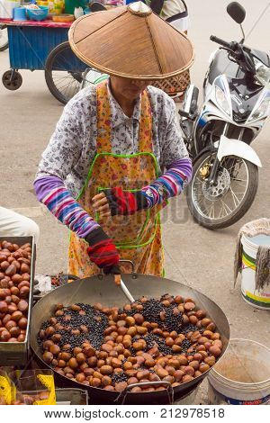 chiang mai January 2013 In this sunny day a thai woman is preparing roasted chestnuts on the street to sell them to the people walking on the sidewalk.