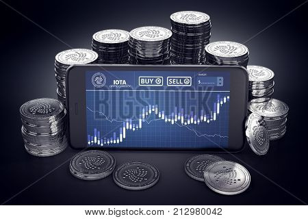 Smartphone with IOTA trading chart on-screen among piles of silver IOTA coins. IOTA trading concept. 3D rendering