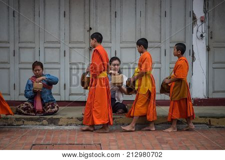 Luang Prabang, Laos - December 21, 2015: Novice monks are walking to collect alms and offerings in the world heritage site, Luang Prabang, Laos.