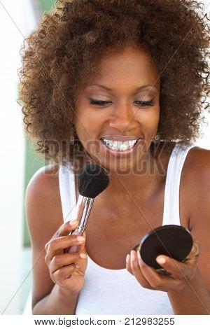 Portarit of a beautiful mature woman applying makeup.