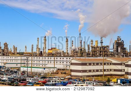 largest producers of synthetic crude oil from oil sands. In the background parking in the foreground smoking pipes.