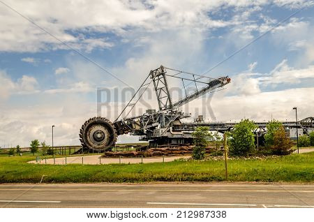 Industrial landscape and heavy equipment for oil sands industry - huge digger. Blue sky and green grass.