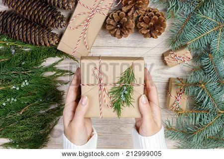 Christmas gift wrapping background. Female hands packaging christmas present wrapped in kraft paper top view. Winter holidays concept flat lay. Woman holding Christmas gift box