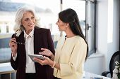 Useful gadget. Positive stylish business women are standing in office and expressing gladness while talking to each other. Young girl is holding tablet and showing screen to gray-haired skillful lady poster
