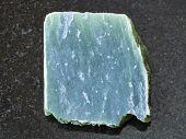 macro shooting of natural mineral rock specimen - raw nephrite stone slab on dark granite background poster