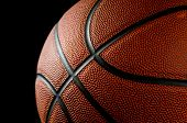Brand new basketball on black background lit from the side poster