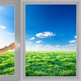 Hand open window over field nature background