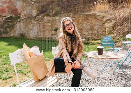 Attractive Lady In Beige Coat Sitting With Comfortable Pose In Park After Food Shopping. Charming Fe