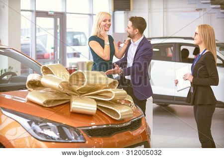 A man makes a gift - a car to his wife. She is surprised at this. They are very happy about this