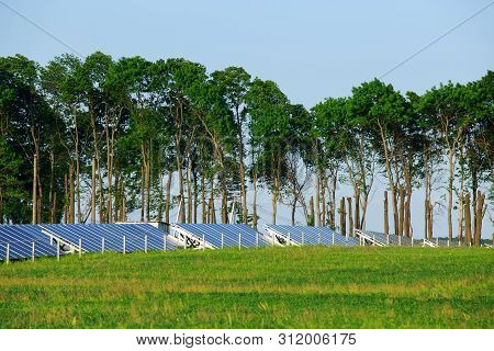 Beautiful modern solar station with blue solar panels stands in a field with green grass poster