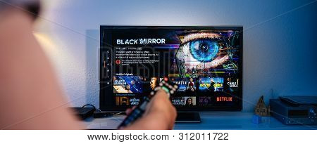Paris, France - Jul 10, 2019: Senior Man Hand Holding Remote Control Watching The Black Mirror On Ne