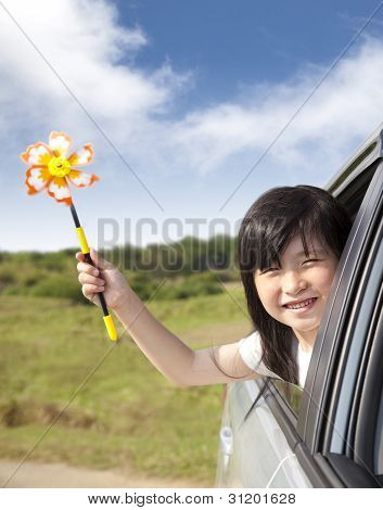 Happy Little Girl Holding Windmill In The Car