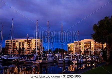 A Florida marina community.  Condos at blue hour overlooking boats in a marina. poster