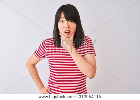 Young beautiful chinese woman wearing red striped t-shirt over isolated white background Looking fascinated with disbelief, surprise and amazed expression with hands on chin poster