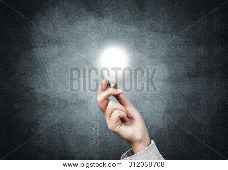 Human Hand With Glowing Incandescent Lamp On Background Grunge Wall. Professional Business Assistanc
