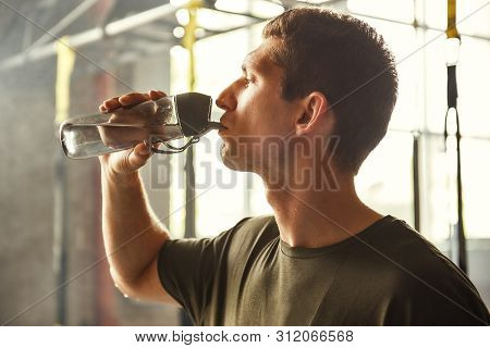 So thirsty. Young athletic man drinking water while exercising at gym poster