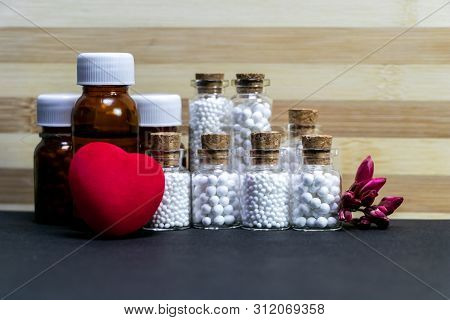 Homeopathic Glass Bottles Of Medicine With Pink Flower Buds, Red Heart On Wood And Dark Background.h