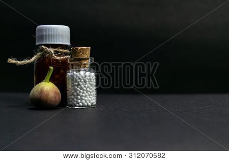 Natural Homeopathic Medicine Concept - Homeopathic Medicine Bottles With Wild Fruit On Dark Backgrou