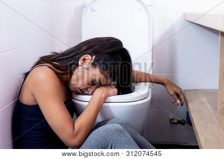 Attractive Young Woman Sitting In The Bathroom Feeling Sick And Looking Depressed And Guilty