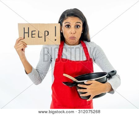Portrait Of Attractive Young Woman Cooking Wearing A Red Apron Holding A Help Sign
