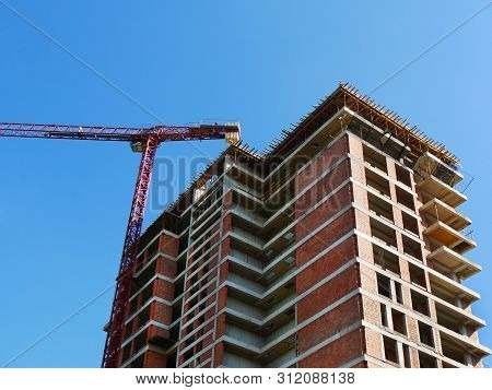 Construction Site Background. Crane Near Building. Red Brick Building Under Construction. Constructi