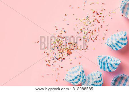 Multicolored Rainbow Sugar Sprinkles Cupcake Blue Paper Cups On Pastel Pink Background. Birthday Par