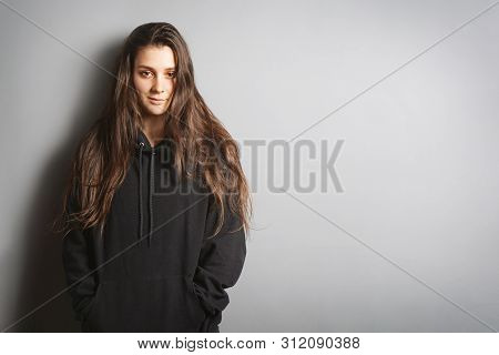 Cool Young Woman With Long Brunette Hair Wearing Black Hoodie Sweater Leaning Against Wall With Her