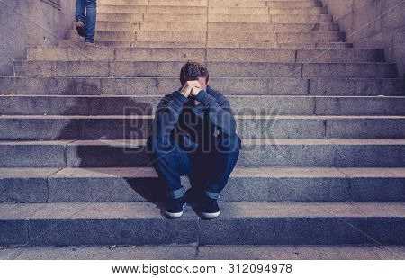 Depressed Sad Young Man Crying Sitting On Stairs Feeling Miserable Lonely In Urban Scene
