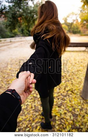 Man Holding Woman's Hand On Fall With Leaves On The Ground