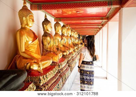Back View Of A Woman Walking Side To Aligned Golden Buddha Statues At The Emerald Temple In Bangkok