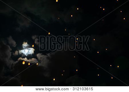 Loi Krathong And Yi Peng Released Paper Lanterns On Cloudy Sky And Moon During Night
