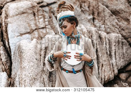Young Beautiful Woman With Lot Of Boho Accessories With The Drum Outdoors