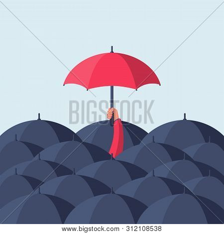 Uniqueness And Individuality. Man Holding A Red Umbrella Among People With Black Umbrellas. Standing