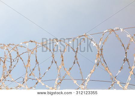 Barbed Wire On The Fence. Front View. Barbwire On Sunny Blue Sky Background. Sun Glare On Metal.