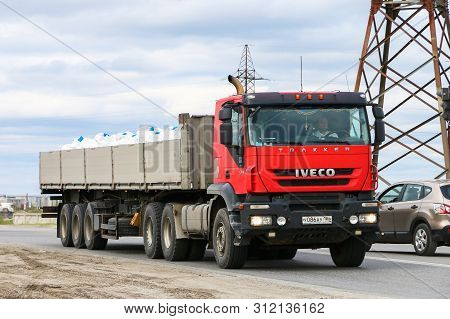Novyy Urengoy, Russia - June 25, 2019: Red Semi-trailer Truck Iveco Trakker In The City Street.
