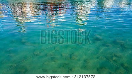 Close Up Of Sea With Stones And Sea Surface With Colorful Reflections.