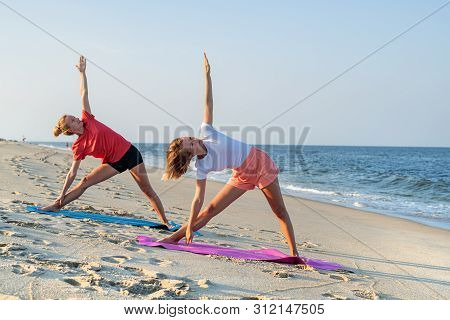 Young Women Practicing Yoga On The Beach. Beautiful Girls Doing Yoga Standing In Warrior Pose At You