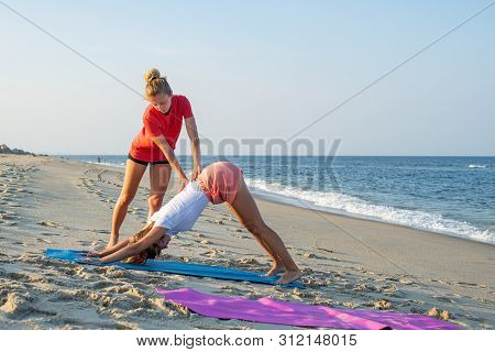 Yoga Class Instructor Helps Beginner To Make Asana Exercises. Woman Doing Downward Facing Dog Exerci