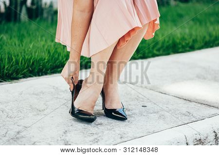 Woman suffering from leg pain outdoors because of uncomfortable shoes. poster
