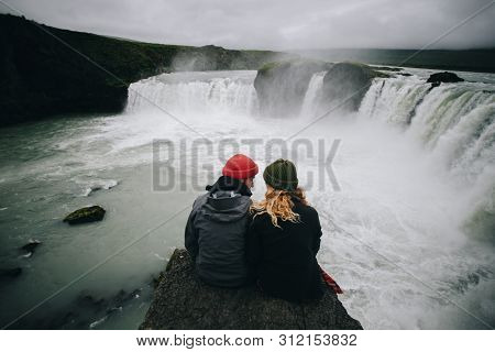 Couple Of Travellers In Winter Warm Clothing Sit On Steep Dangerous Cliff Next To Waterfall, Watch F