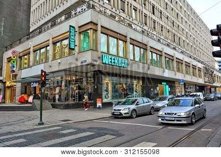Exterior Of A Shopping Center. Weekday Store. Swedish Denim & Fashion Brand. White Cars. Traffic. No